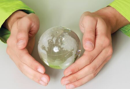 glass globe: Male hands holding paper people around a glass globe