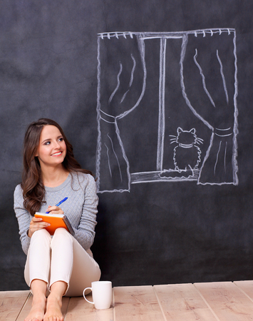 Young woman sitting on the floor near dark wall with painted a window photo