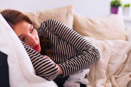 nauseous: Portrait of a sick woman while sitting on the sofa
