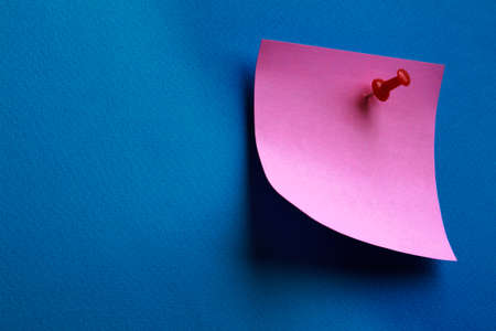 memo pad: Pink memo sheet on blue background isolated. Stock Photo