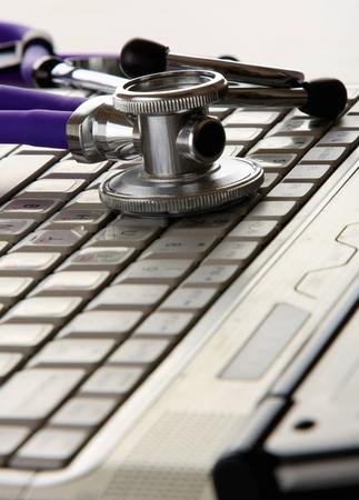 white laptop: Uno stetoscopio viola su un computer portatile bianco