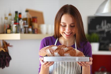 tranches de pain: Jeune femme tenant savoureux pain frais dans sa cuisine. Banque d'images