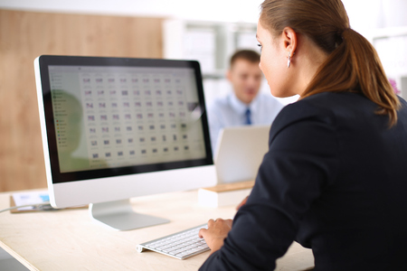 vrouwen: Jonge vrouw werkt in het kantoor, zit op bureau, met behulp van laptop.