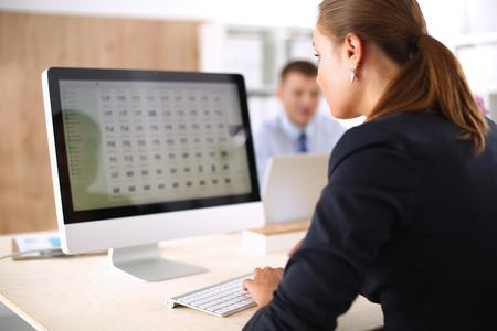 computadora: Mujer joven que trabaja en la oficina, sentado en el escritorio, usando la computadora portátil.