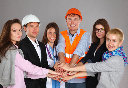 various occupations: Portrait of smiling people with various occupations putting their hands on top of each other.