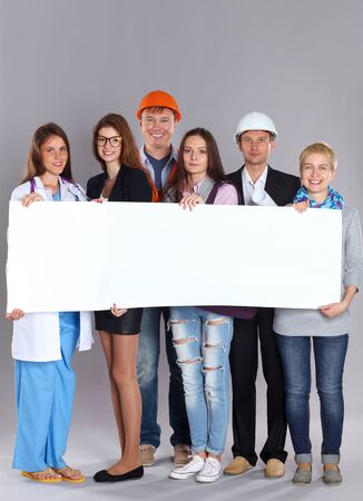 business service: Portrait of smiling people with various occupations holding blank billboard . Stock Photo