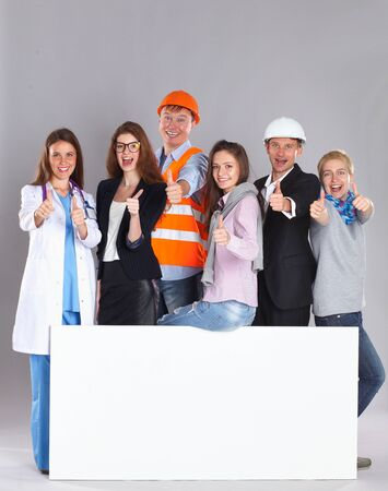 various occupations: Portrait of smiling people with various occupations holding blank billboard showing ok . Stock Photo