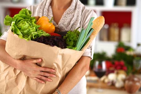 bolsa de pan: Mujer joven que sostiene el bolso de compras de comestibles con las verduras de pie en la cocina. Foto de archivo