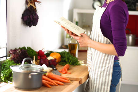 cutting vegetables: Young woman cutting vegetables in the kitchen . Stock Photo