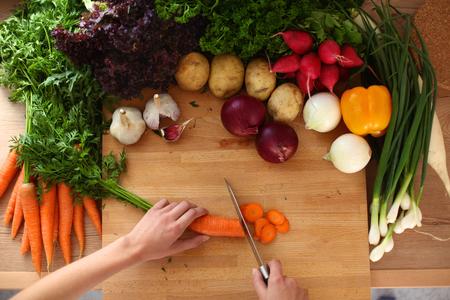 キッチンで若い女性カット野菜。