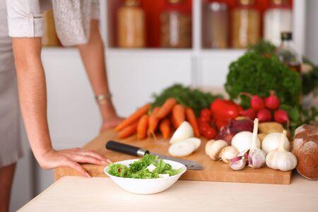 cabello rubio: Mujer joven cortar verduras en la cocina.