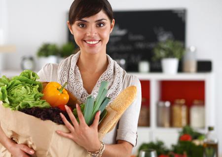 comiendo pan: Mujer joven que sostiene el bolso de compras de comestibles con las verduras de pie en la cocina. Foto de archivo