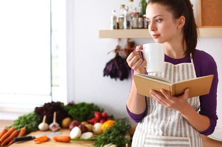 Junge Frau lesen Kochbuch in der Küche, auf der Suche nach Rezept. Lizenzfreie Bilder - 43998590