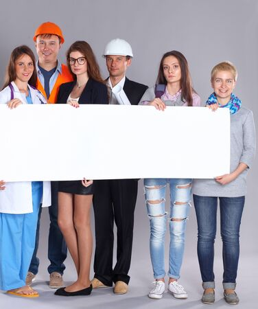 various occupations: Portrait of smiling people with various occupations holding blank billboard . Stock Photo