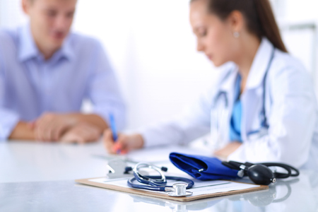 medico y paciente: Mujer del doctor que se sienta con el paciente de sexo masculino en el mostrador.