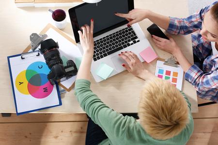 ノート パソコンを机の上に座っている女性写真家。