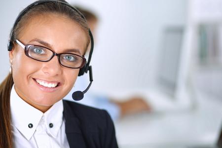 servicio al cliente: Feliz mujer llevaba auriculares y sentado en el escritorio.