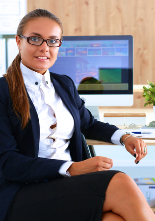 office desk: Young woman working in office, sitting at desk. Stock Photo