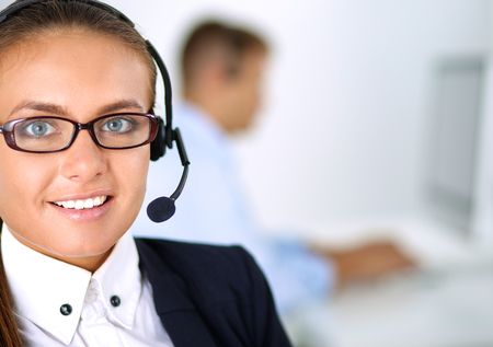 tech support: Happy female wearing headset and sitting on the desk .