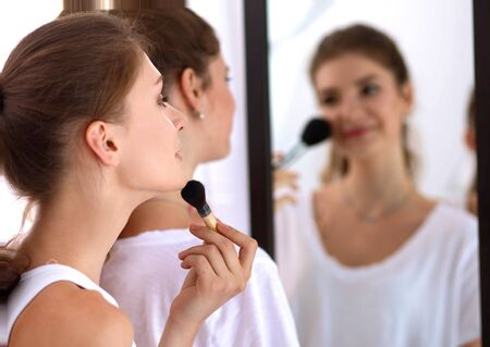 mirror: Beautiful girl looking in the mirror and applying cosmetic with a big brush. Stock Photo