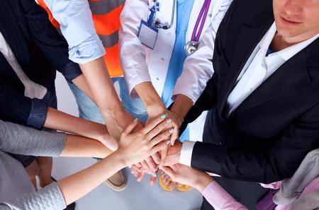 constructor: Retrato de las personas con diversas ocupaciones poniendo sus manos encima de uno al otro.