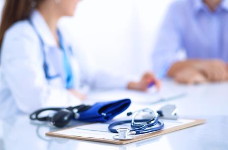 デスクで男性患者と座っている医者の女性。