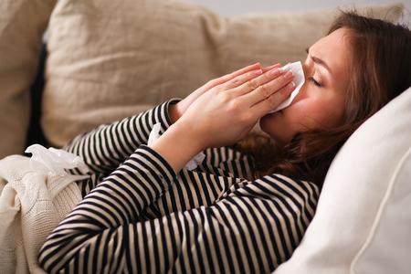enfermos: Retrato de una mujer enferma que sopla su nariz mientras estaba sentado en el sofá. Foto de archivo