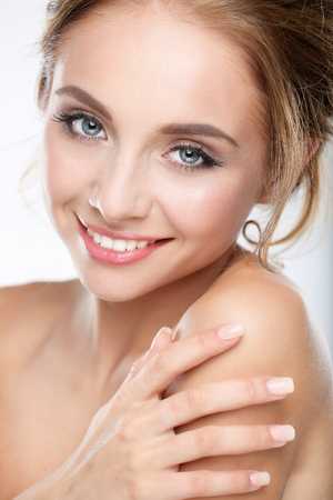 unblemished: Studio shot of a beautiful young woman with perfect skin against a white background