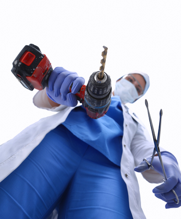 scaring: View from below of masked doctor scaring the patient with a drill Stock Photo
