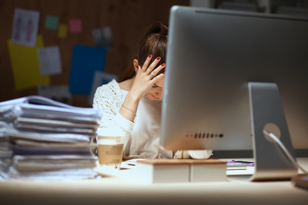 work addicted: A portrait of a businesswoman staying late in the office with a pile of work to do Stock Photo