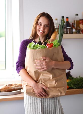 食料品の袋を保持している彼女の台所に立っている若い女性。 写真素材