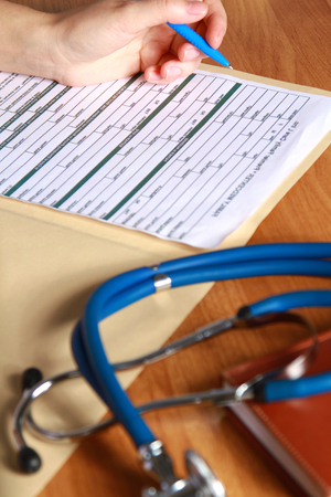 scientific literature: Close-up of writing doctors hands on a wooden desk