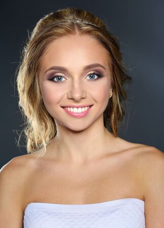 unblemished: Studio shot of a beautiful young woman with perfect skin against a gray background