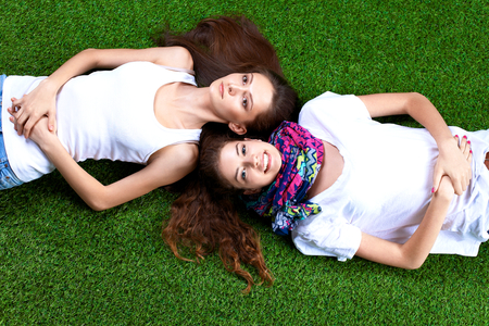 lying on grass: Two pretty girls lying on the fresh green grass . Stock Photo