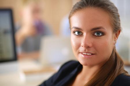 机に座ってのオフィスで働く若い女性。
