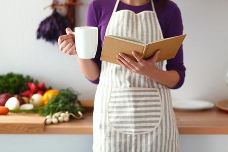 レシピをお探しする台所で料理の本を読む若い女性。