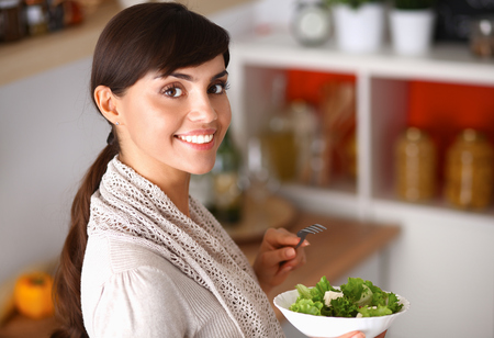 eating utensils: Young woman eating fresh salad in modern kitchen .