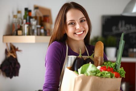 abarrotes: Mujer joven que sostiene el bolso de compras de comestibles con las verduras de pie en la cocina. Foto de archivo