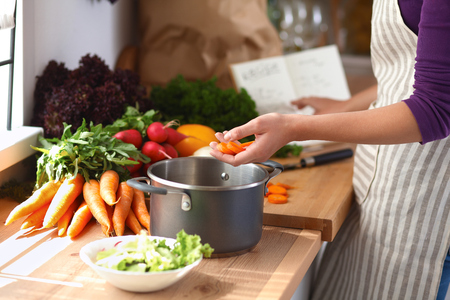 healthy foods: Young woman cutting vegetables in the kitchen . Stock Photo