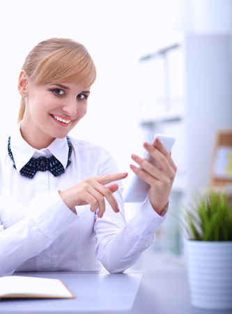 woman at the phone: Woman in office using mobile phone .