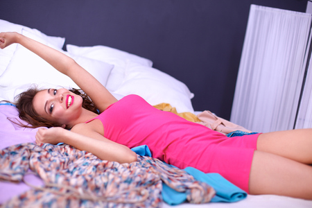 bed clothes: Happy woman lying bed surrounded by her clothes . Stock Photo