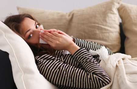 feeble: Portrait of a sick woman blowing her nose while sitting on the sofa.