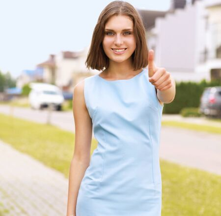 allright: A young woman showing ok , standing near house Stock Photo