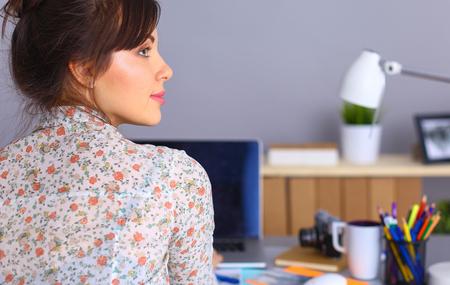 female photographer: Female photographer sitting on the desk with laptop . Stock Photo