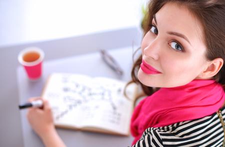若い女性は、白いテーブルに日記に書き込みます。 写真素材