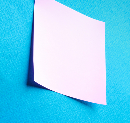 note paper: Pink paper note on blue background isolated. Stock Photo