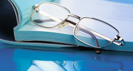 Open journals with glasses in front, isolated on blue Stock Photo
