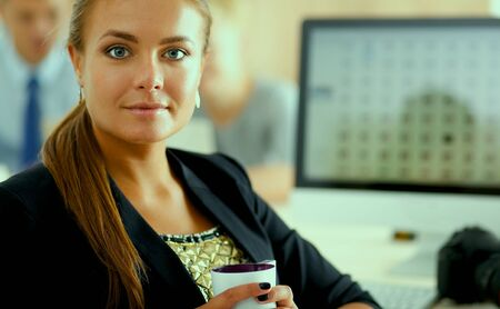 downloaded: Female photographer sitting on the desk with laptop . Stock Photo
