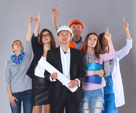 various occupations: Portrait of smiling people with various occupations and pointing up. Stock Photo