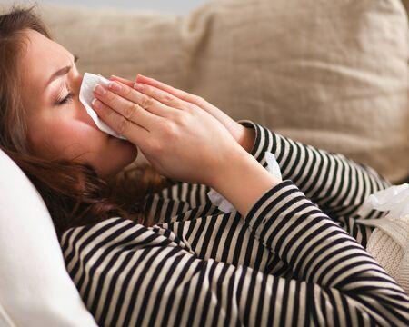 chory: Portret chorej dmuchanie jej nosa, siedząc na kanapie. Zdjęcie Seryjne